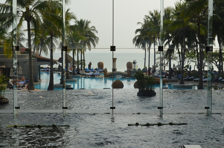 The lobby of the Hilton Hotel with water falls into a pool and on into the sea